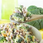 A wooden spoon holding a bite of broccoli salad.