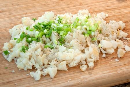 Mixing potatoes, onions, salt and pepper.