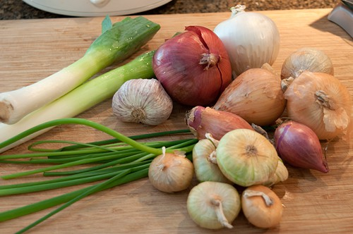 Several varieties of onions on a cutting board.