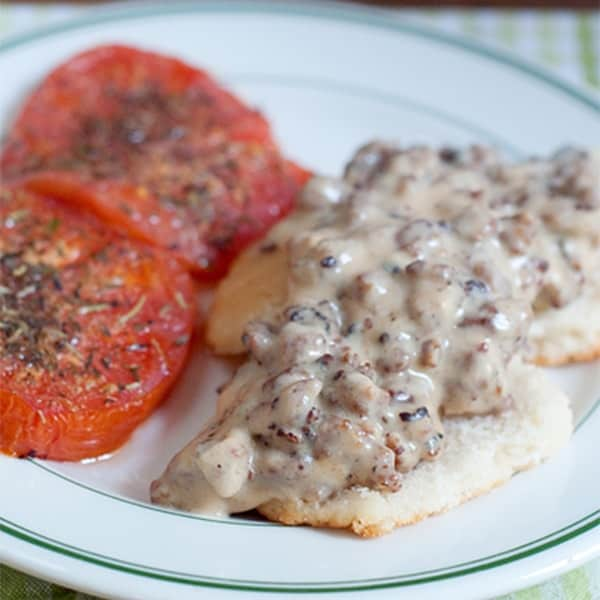 A hearty country breakfast of sausage gravy and biscuits with baked, herbed tomato slices on the side. From @NevrEnoughThyme https://www.lanascooking.com/sausage-gravy-and-biscuits-with-tomatoes
