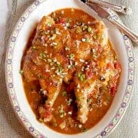 Creole Style Smothered Chicken - a whole butterflied chicken cooked under weight in a skillet and smothered with a creole sauce. From @NevrEnoughThyme https://www.lanascooking.com/creole-style-smothered-chicken/