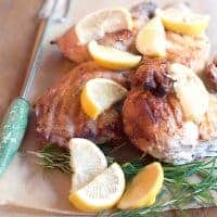 Rosemary Lemon Spatchcocked Chicken - butterflied chicken marinated in olive oil, rosemary, and lemon - cooked under a weight on an outdoors grill. From @NevrEnoughThyme https://www.lanascooking.com/rosemary-lemon-spatchcocked-chicken-recipe/