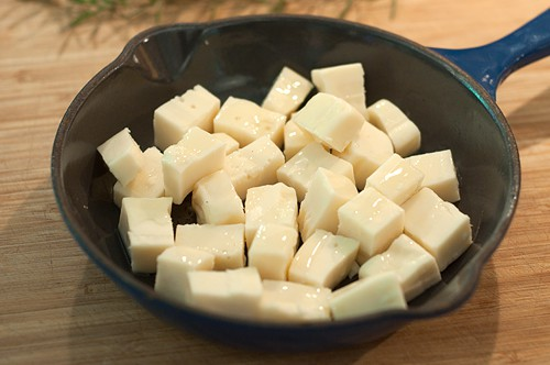 Drizzle the cheese with olive oil for Baked Fontina