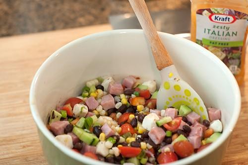 Stir together ingredients for Ham and Black Bean Summer Salad