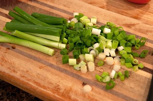 Chopped green onions on a cutting board.