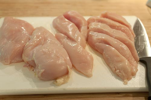 Cutting chicken into strips on a cutting board.