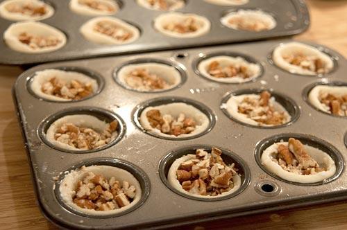 Adding chopped pecans to tart shells.