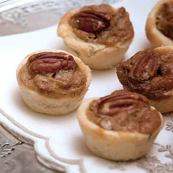 Pecan Tassies are a traditional southern holiday recipe. These two-bite mini pecan pies make a delicious addition to your dessert tray. https://www.lanascooking.com/pecan-tassies/