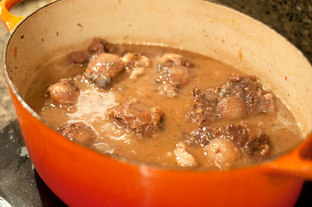 Return oxtails to thickened broth