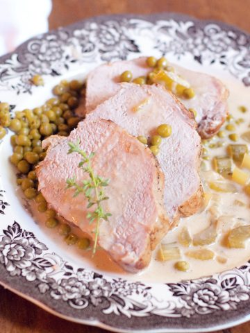 Sliced Braised Pork Loin with Creamy Celery Sauce on a serving plate.
