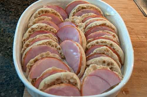Arrange English muffins and Canadian bacon in baking dish for Easy Weekend Breakfast Strata