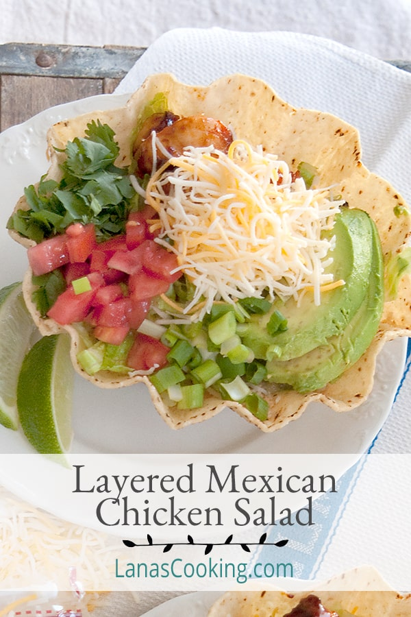 Layered Mexican Chicken Salad - a great main dish lunch or dinner salad featuring couscous and seasoned chicken with cheese, salsa, and cilantro. From @NevrEnoughThyme https://www.lanascooking.com/layered-mexican-chicken-salad/