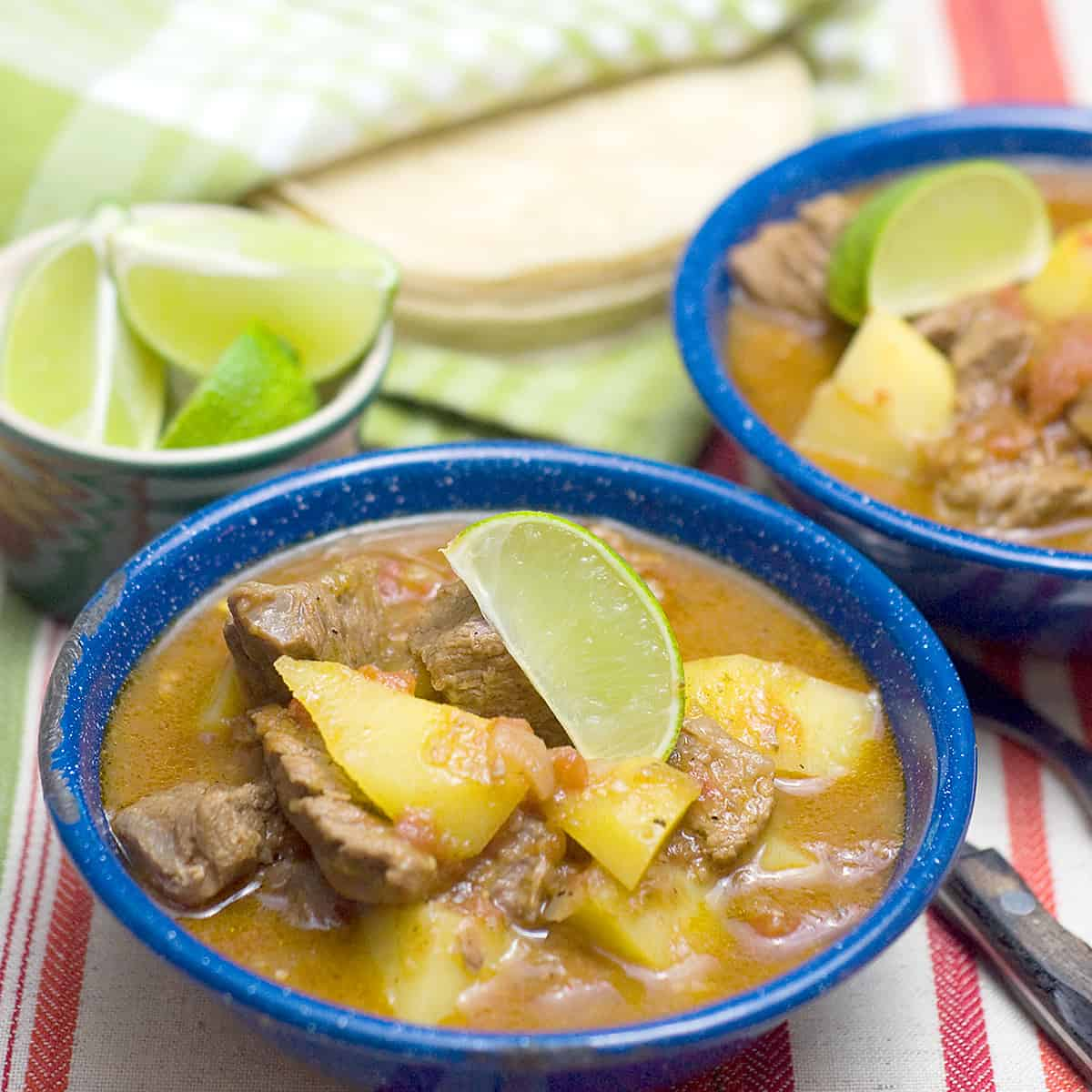 Two blue bowls filled with mexican beef stew (caldillo) with lime wedges and tortillas on the side.