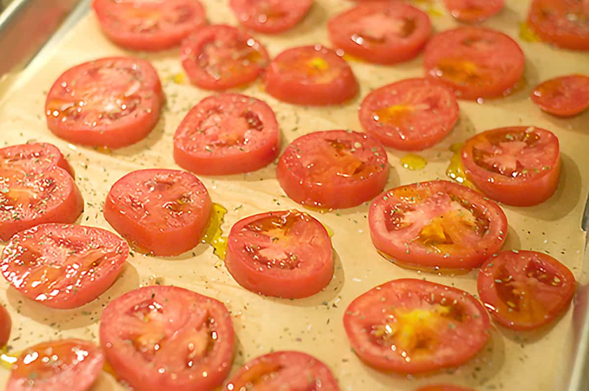 Tomato slices on a baking sheet sprinkled with olive oil, salt, pepper, and herbs