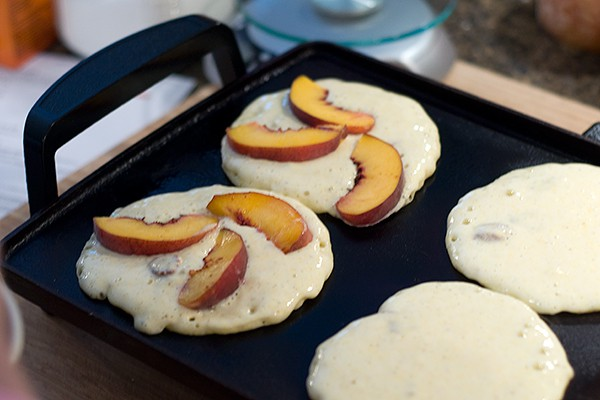 Arrange peach wedges for Pecan-Peach Pancakes