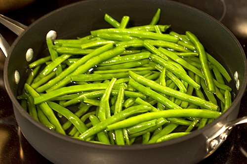 Fresh green beans cooking in a deep skillet.