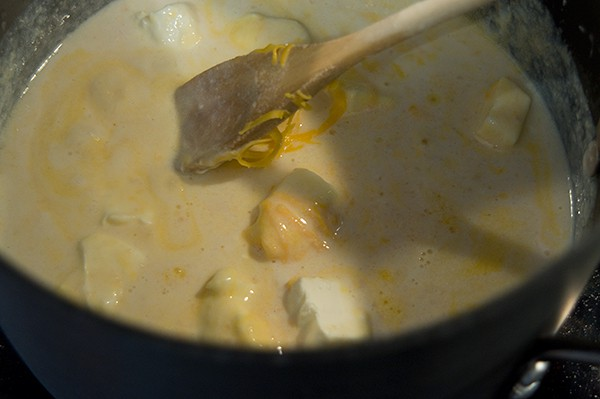 Adding cheddar and cream cheeses to the sauce.