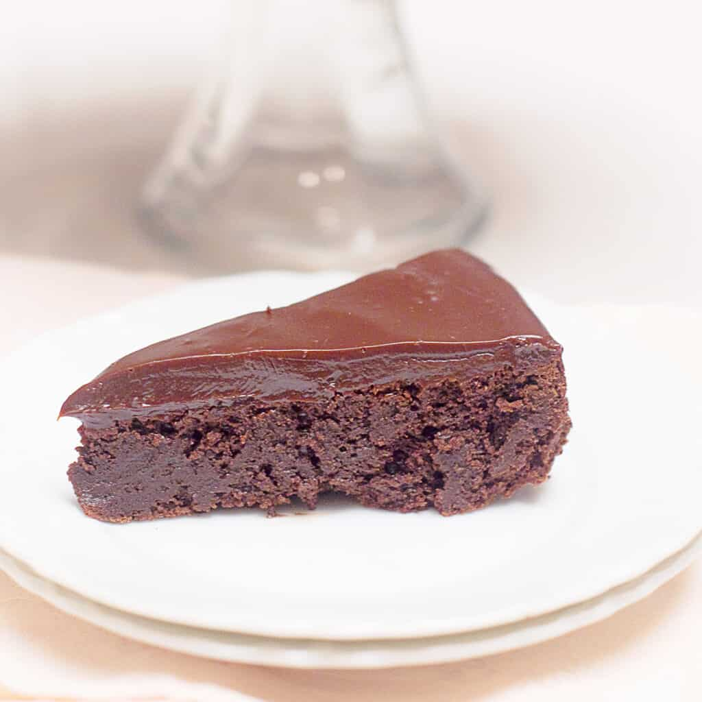 A serving of flourless chocolate cake on a white plate with remainder of cake on a cake stand in background.