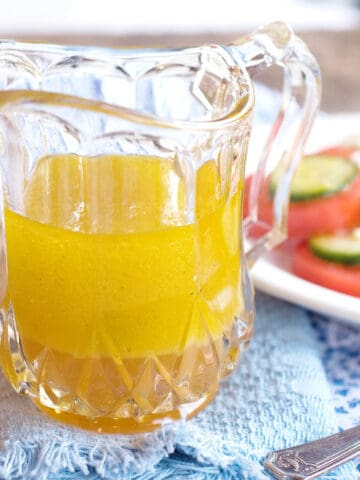 A small glass pitcher filled with lemon vinaigrette; salad in the background.