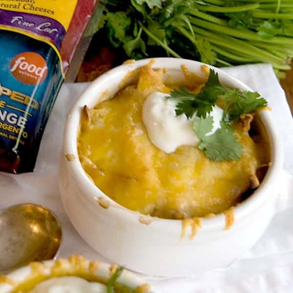 Chicken Tortilla Onion Soup - My Mexican riff on onion soup - with tortilla strips, chicken, onions, and poblano peppers - topped with a Mexican cheese blend. From @NevrEnoughThyme https://www.lanascooking.com/chicken-tortilla-onion-soup/