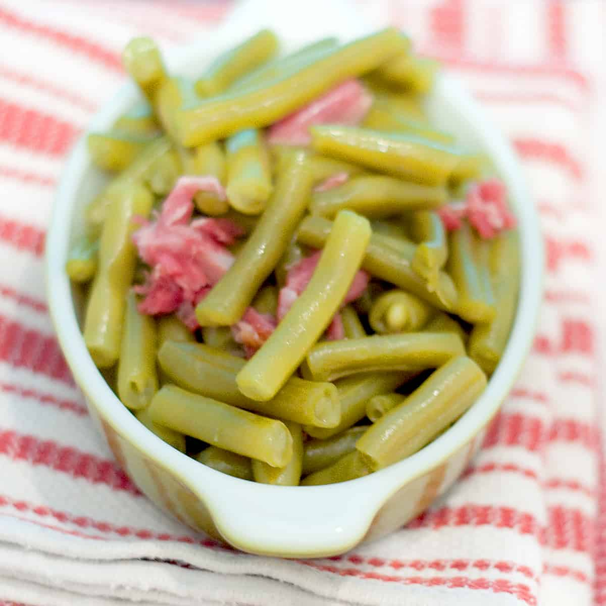 Old Fashioned Southern Green Beans with smoky bacon in a small bowl resting on a kitchen towel.