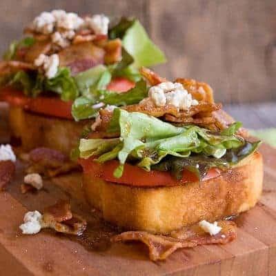 Garlic BLT Stacks - garlic bread topped with fresh tomato, bacon, lettuce, feta, and balsamic vinegar. From @NevrEnoughThyme https://www.lanascooking.com/garlic-blt-stacks