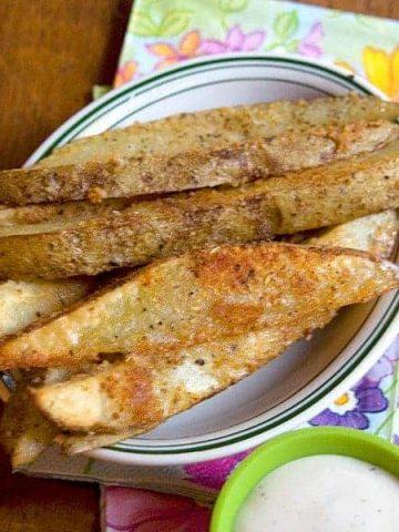 Parmesan Garlic Baked Potato Wedges from @NevrEnoughThyme https://www.lanascooking.com/parmesan-garlic-baked-potato-wedges