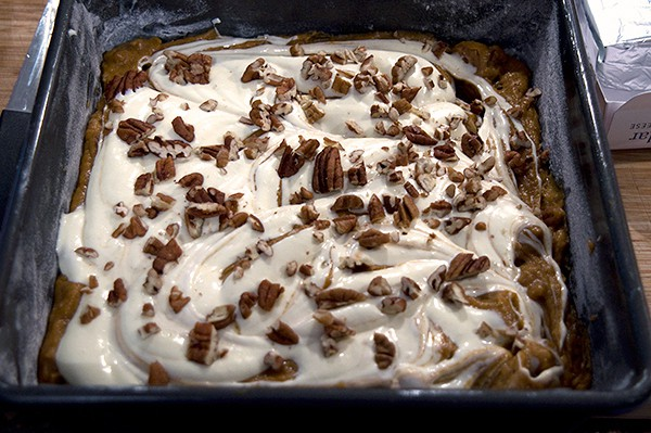 Sprinkle top of Pumpkin Cream Cheese Brownies with pecans
