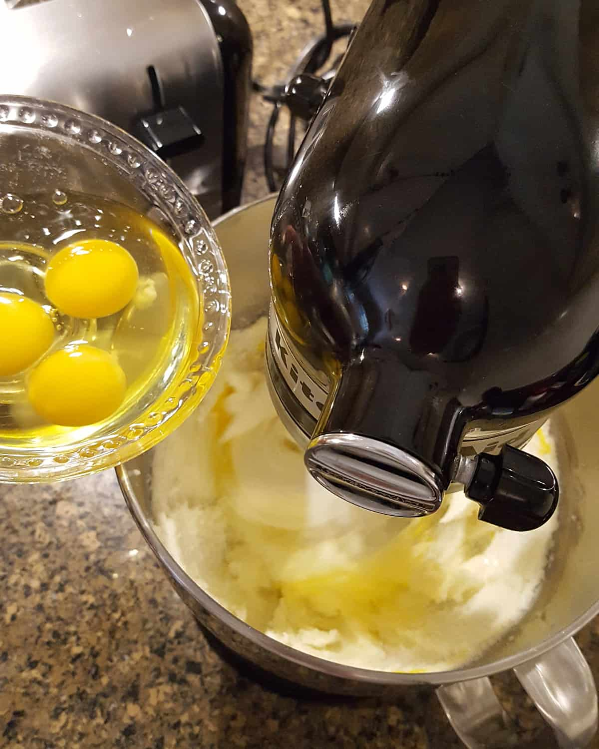 Eggs being added from a small bowl into the butter and sugar mixture in a stand mixer.