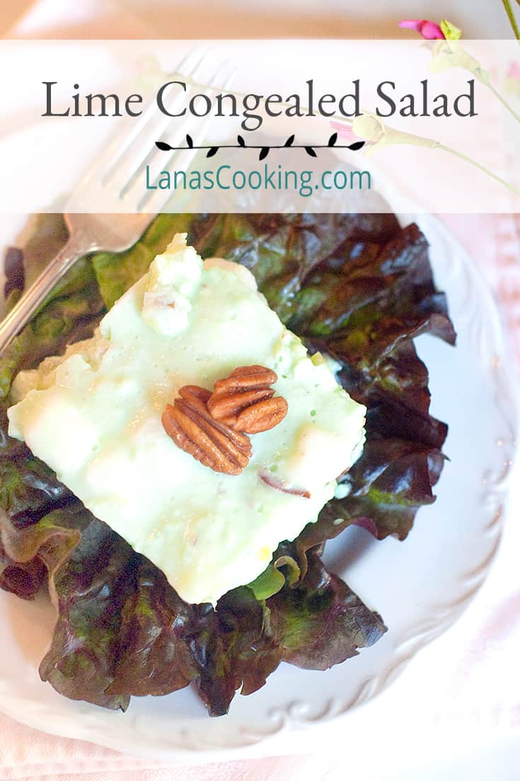 A serving of Lime Congealed Salad on a red lettuce leaf. Text overlay for pinning.