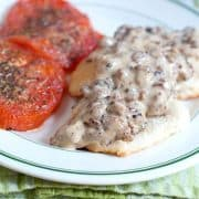 Sausage Gravy and Biscuits with Tomatoes - A hearty country breakfast of sausage gravy served over biscuits with baked, herbed tomato slices on the side. https://www.lanascooking.com/sausage-gravy-and-biscuits-with-tomatoes