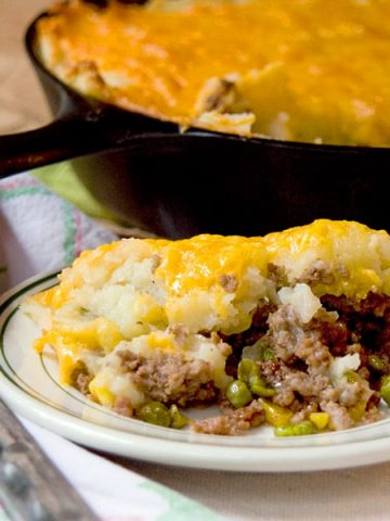 Classic Shepherd's Pie, or Cottage Pie, with ground beef and vegetables topped with creamy mashed potatoes and cheese. From @NevrEnoughThyme https://www.lanascooking.com/shepherds-pie/