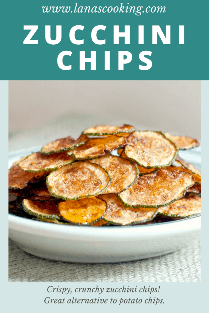 Finished zucchini chips stacked on a serving plate.