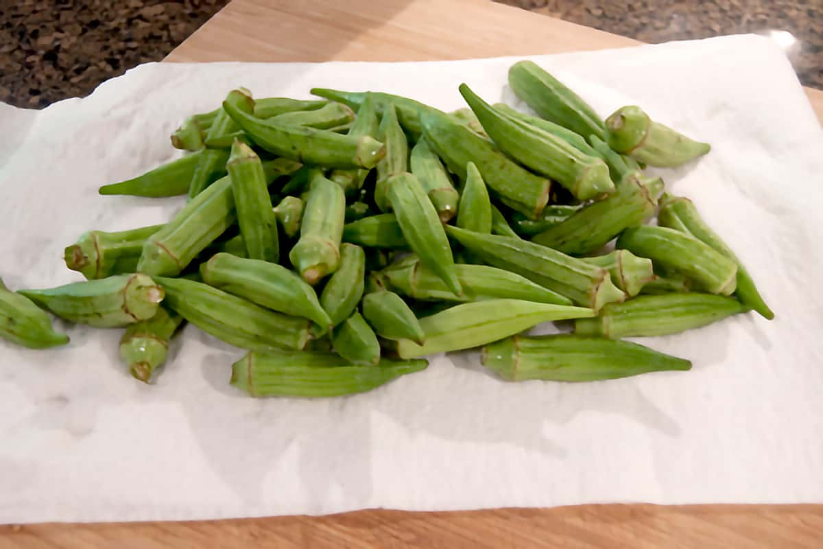 Whole okra pods washed and draining on paper towels
