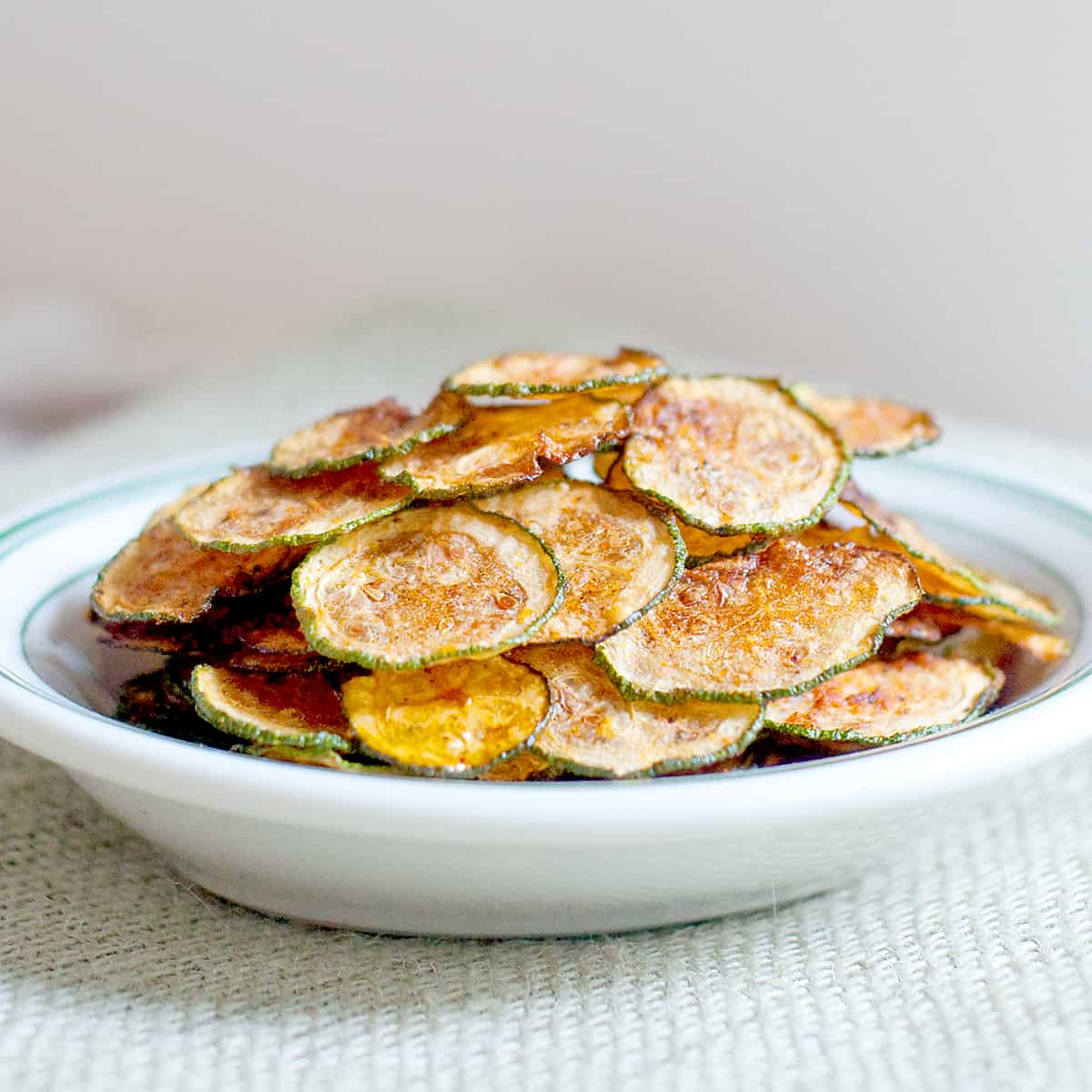 Baked zucchini chips stacked in a white bowl.