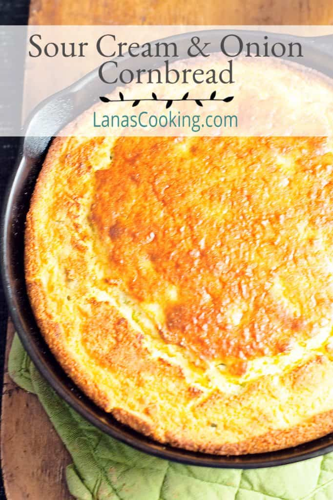 Sour Cream and Onion Cornbread in a cast iron skillet on a hot pad. Text overlay for pinning.