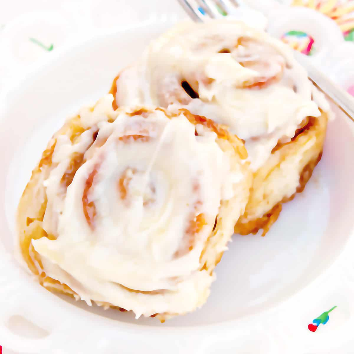 Two cinnamon rolls on a serving plate with a fork on the side.