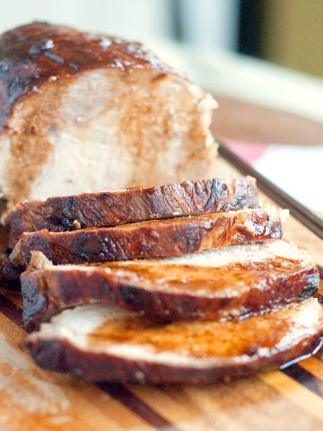 Sliced pork loin on a serving board.