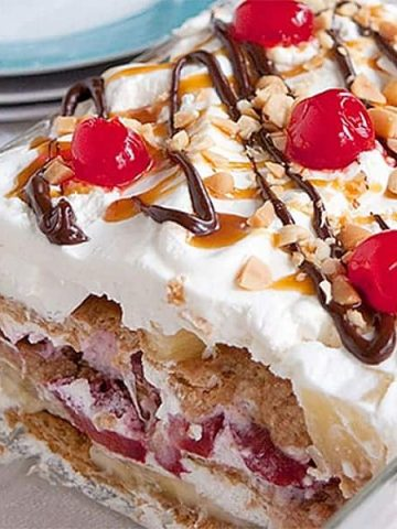 Banana Split Icebox Cake - an old fashioned dessert with layers of whipped cream, banana, strawberries, and pineapple. From @NevrEnoughThyme https://www.lanascooking.com/banana-split-icebox-cake