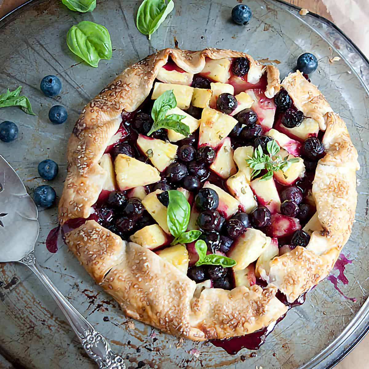 A freeform Pineapple Blueberry Basil Galette using purchased pie crust. A most unusual dessert full of fruity, herby flavors. From @NevrEnoughThyme https://www.lanascooking.com/pineapple-blueberry-basil-galette/