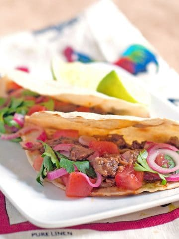 Two slow cooker shredded beef tacos on a serving plate with a kitchen towel underneath.
