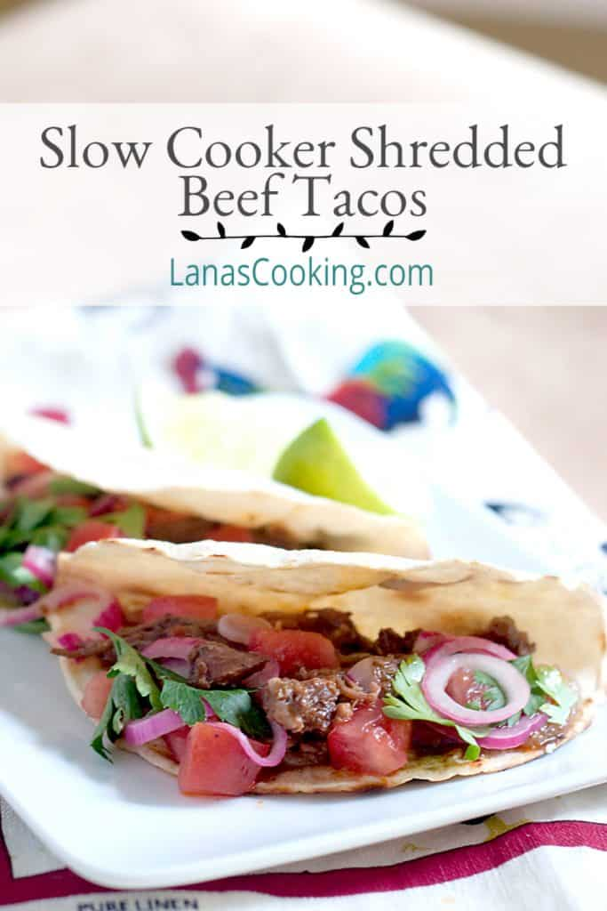 Two slow cooker shredded beef tacos on a serving plate with a kitchen towel underneath. Text overlay for pinning.