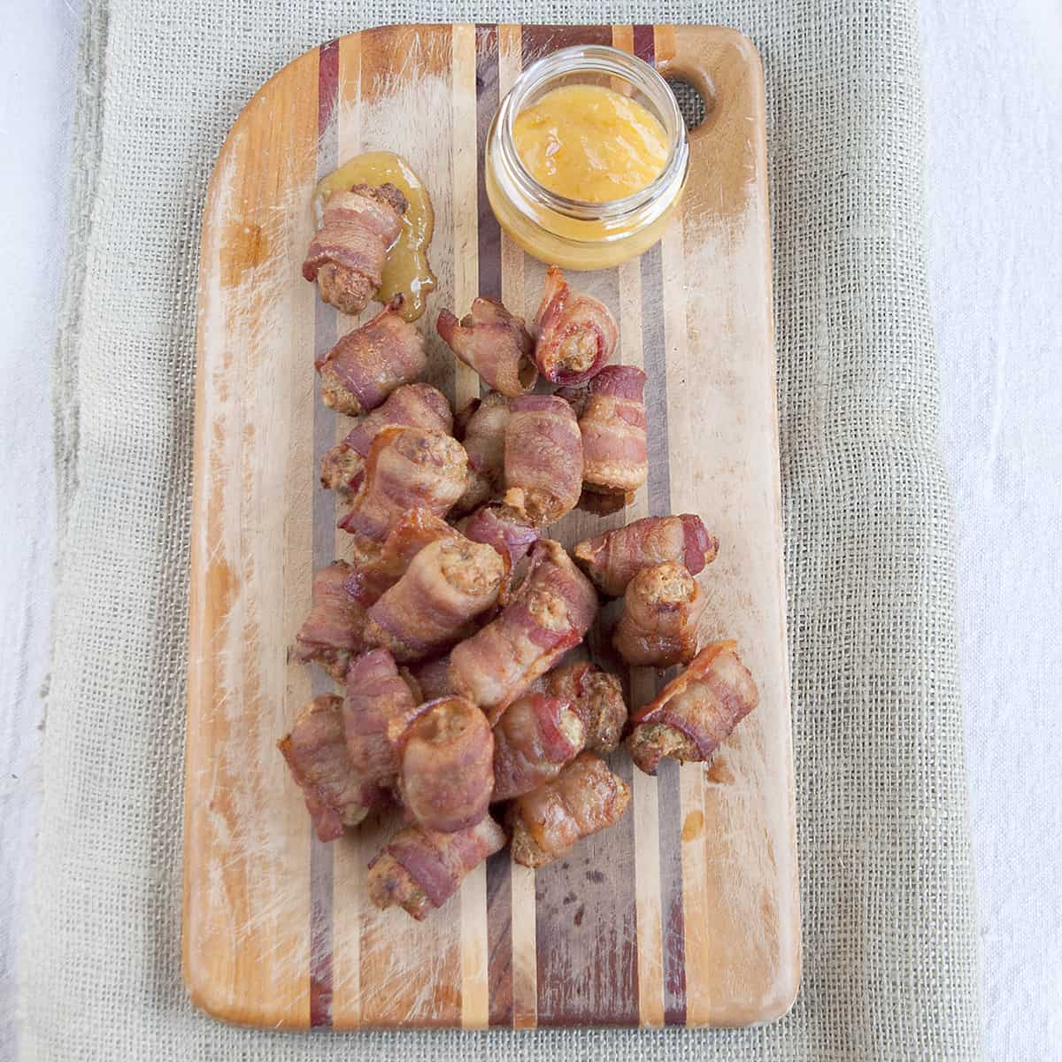 Bacon Wrapped Sausage Balls - Spicy, herby, cheesy sausage balls wrapped in bacon and served with a peach-Dijon dipping sauce. From @NevrEnoughThyme https://www.lanascooking.com/bacon-wrapped-sausage-balls