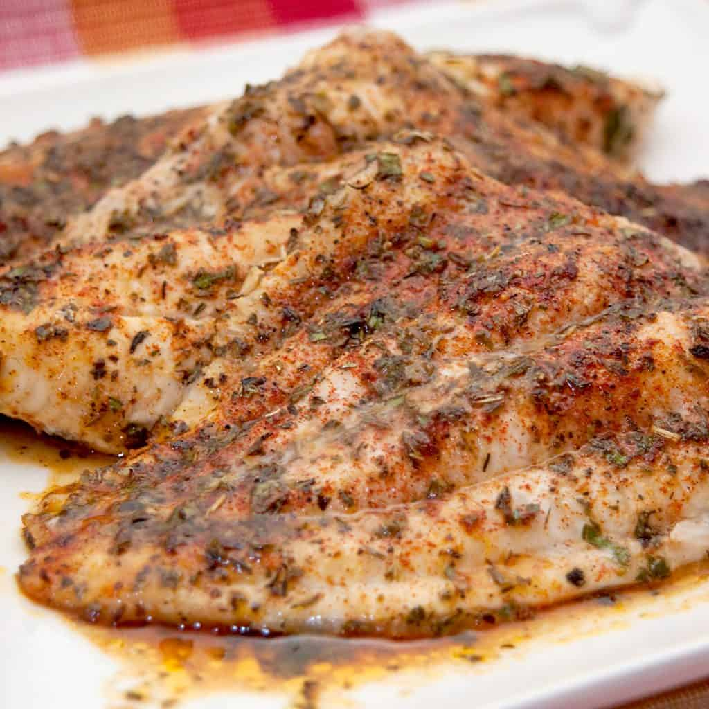 Baked catfish on a white serving plate.