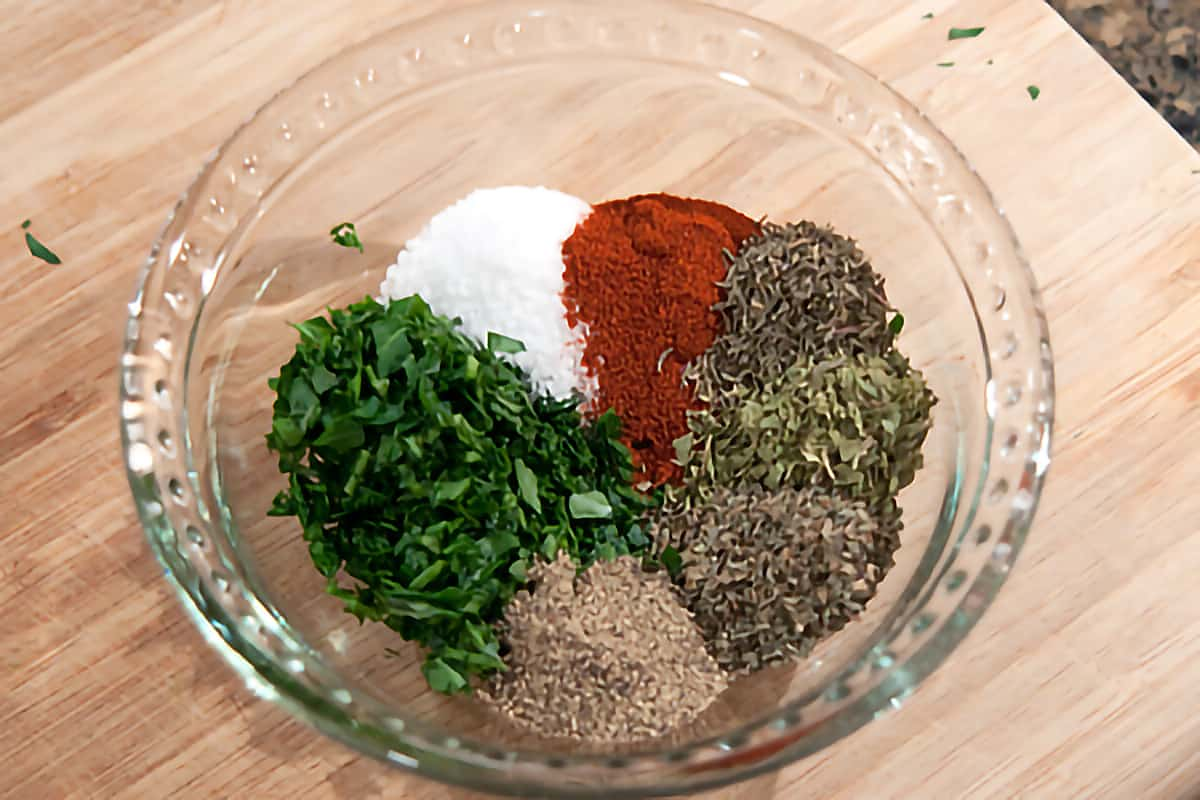 Small bowl with parsley, salt, paprika, thyme, oregano, basil and pepper needed for recipe