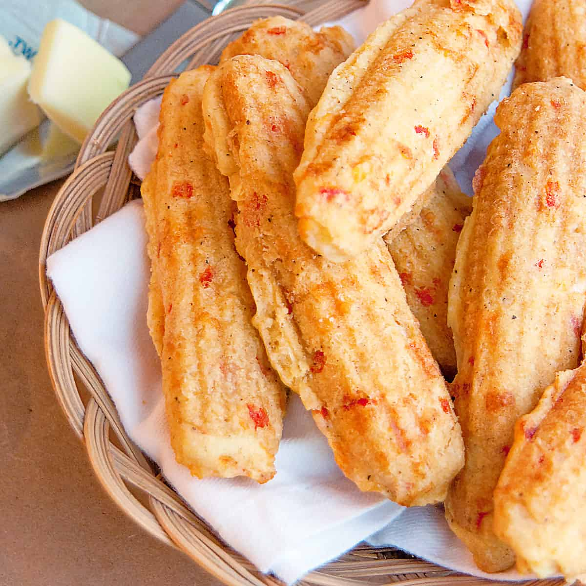 Pimiento Cheese Corn Sticks in a basket with a knife and butter to the side.