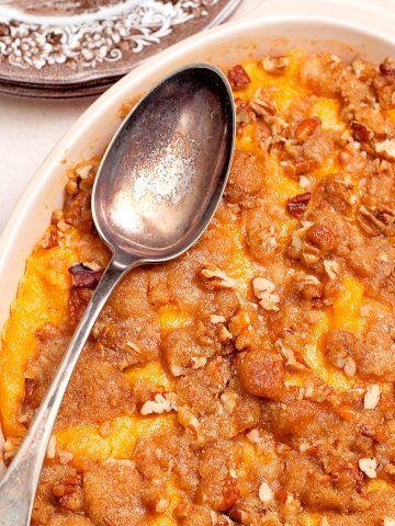 Sweet Potato Casserole in a serving dish with vintage serving spoon.