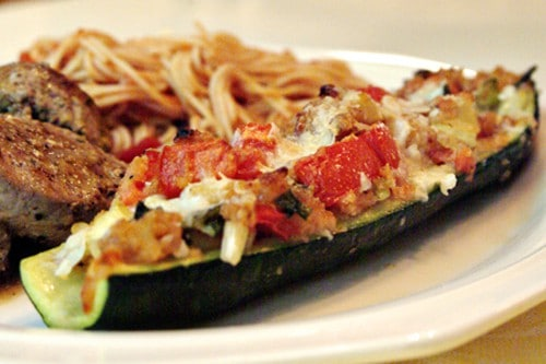 Stuffed zucchini - fresh zucchini from the garden filled with a stuffing of onion, tomato, bread crumbs and parmesan cheese. From @NevrEnoughThyme https://www.lanascooking.com/stuffed-zucchini/
