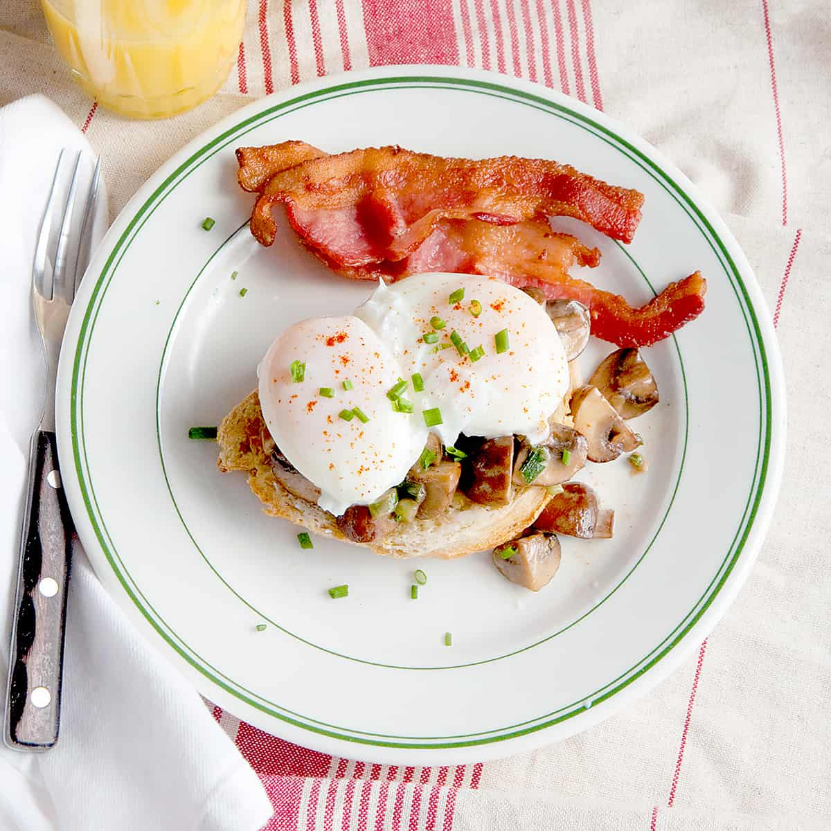 A serving of creamed mushrooms and poached eggs with a side of bacon on a serving plate.