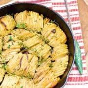 Crispy roasted potatoes in a black cast iron skillet set on a kitchen towel with a serving fork alongside.